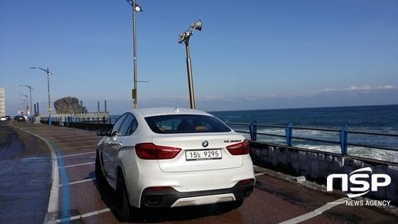 강원도 동해시 묵호항 인근 해변도로 옆 성난 파도(위)와 BMW 뉴 X6 M50d(아래) (사진 = 강은태 기자)