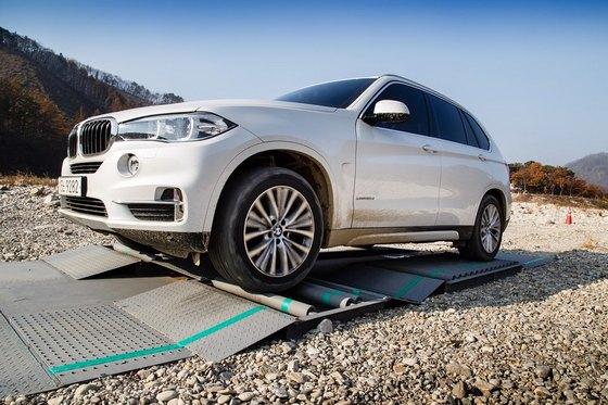 차량 바퀴 3개가 빙판에 걸려 있어 바퀴 하나만으로 위험 지역을 탈출해야 하는 가상의 조건을 설정한 인공구조물 롤러에서 BMW X5 차량이 가상위험 지역을 탈출하고 있다. (사진 = BMW 코리아)