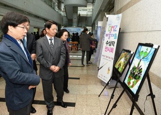 양복완 경기도 행정2부지사(가운데)가 DMZ 미술대회 작품을 감상하고 있는 모습. (사진 = 경기도청)