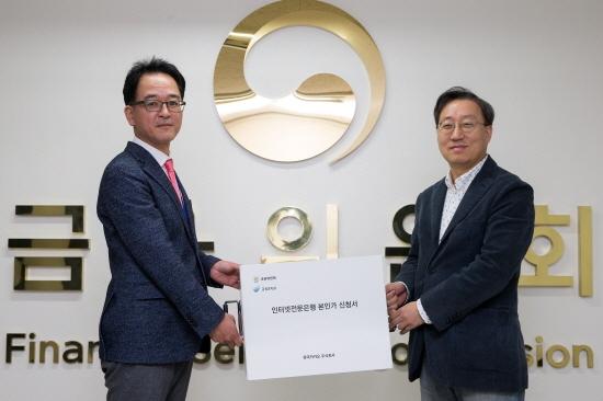 김진홍 금융위 은행과장(왼쪽)과 윤호영 카카오뱅크 공동대표(오른쪽)가 인터넷전문은행 본인가 신청서를 들고 기념촬영을 하고 있다.
