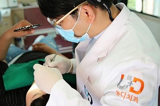 진세식 유디치과협회장이 학생의 치아를 검진 한 후 치료를 하고 있는 모습 (사진 = 유디치과)