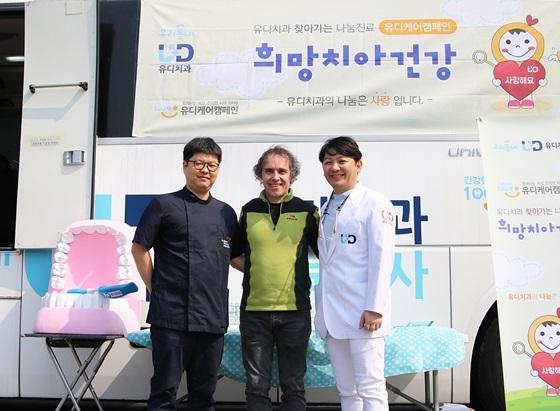 사진 왼쪽부터 박호선 유디치과 고덕점 대표원장, 사회복지법인 안나의 집 김하종 신부, 진세식 유디치과 협회장이 유디덴탈버스 앞에서 기념촬영을 하고 있다 (사진 = 유디치과)