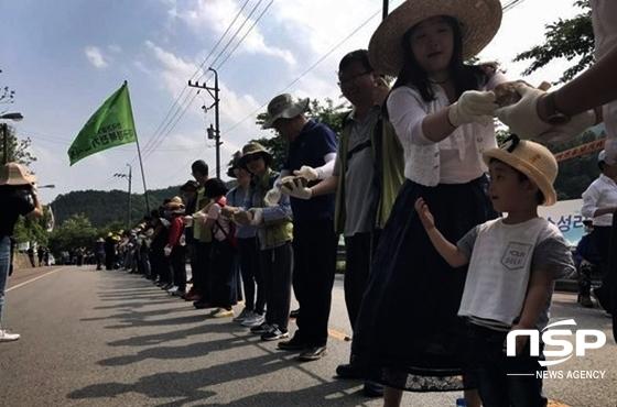 많은 참가자들이 인간 띠를 이고 있는 가운데 한 어린 아이가 인간 띠 잇기 행사에 참여했다. (사진 = 사드배치 철회 성주투쟁위원회 제공)