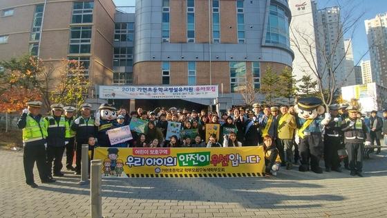 가현초등학교 입구에서 현춘희 경찰서장을 비롯한 관계자들과 학생들이 교통안전 캠페인 후 기념촬영을 하고 있다. (사진 = 김포경찰서)