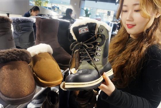 롯데백화점 대구점 5층 슈즈 코너에서 20대 여성 고객이 갑자기 추워진 날씨에 따뜻한 겨울을 보내기 위해 다양한 디자인의 방한슈즈를  살펴보고 있다. (사진 = 롯데백화점 대구점)