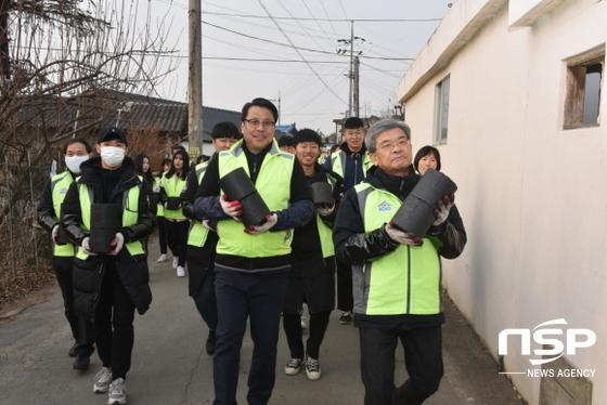 직접 연탄을 들고 배달하고 있는 변창훈 총장과 김정우 총장. (사진 = 대구한의대학교)