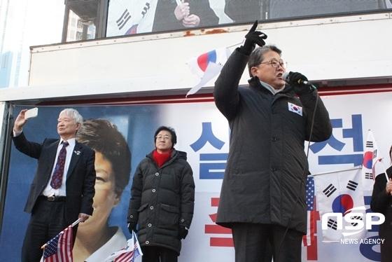 무대에서 휴대폰으로 집회 현장을 촬영하는 서석구 변호사(왼쪽)와 발언하는 조원진 대한애국당 대표 (왼쪽에서 세번쨰) (사진 = 김덕엽 기자)
