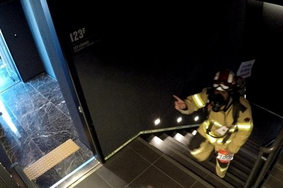 지난해 화재진압복과 방독면을 착용하고 완주에 성공한 소방대원 참가자 (사진 = 롯데물산)