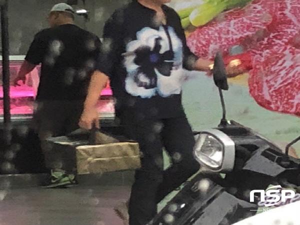 입찰에 참가한 건설회사 홍보직원으로 추정되는 여성이 정육세트를 들고 정육점을 나서고 있다. (사진 = 독자제공)