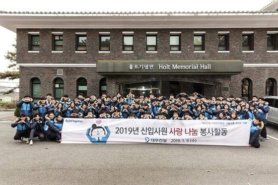 2019년 대우건설 신입사원들이 봉사활동 기념촬영을 하고 있다. (사진 = 대우건설)