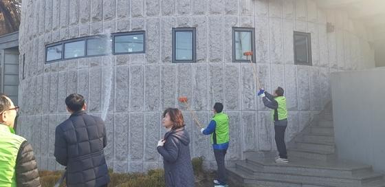 14일 수원시 관계자들이 장안구 반딧불이 화장실 건물 외벽을 청소하고 있다. (사진 = 수원시)