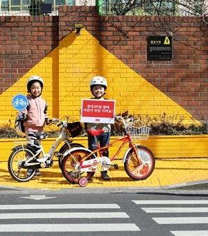 서울 흥인초등학교 앞 교통안전을 위해 설치된 옐로카펫에서 두 어린이가 3M 안전 반사지 스티커가 부착된 자전거를 끌며 자전거 안전의 중요성을 알리고 있다 (사진 = 한국쓰리엠)