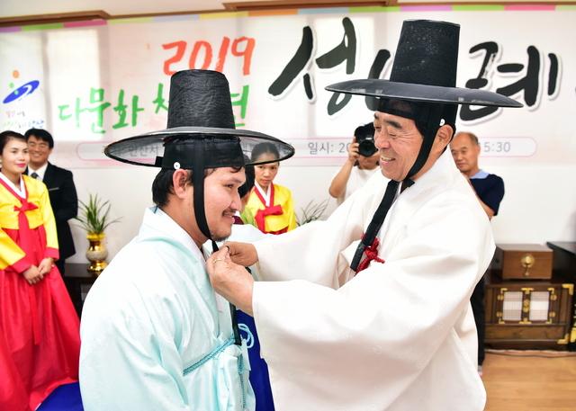 8일 개최된 전통성년례에서 윤화섭 안산시장(오른쪽)이 직접 다문화청소년에게 관을 씌워주고 있다. (사진 = 안산시)