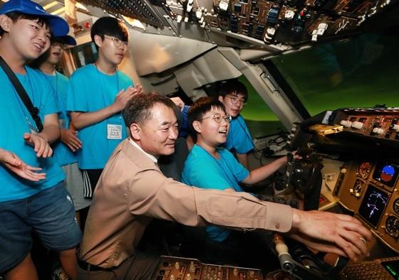 참가자들이 아시아나항공 운항승무원들이 실제로 비행훈련을 실시하는 항공기 시뮬레이터를 체험하고 있다. (사진 = 아시아나항공)