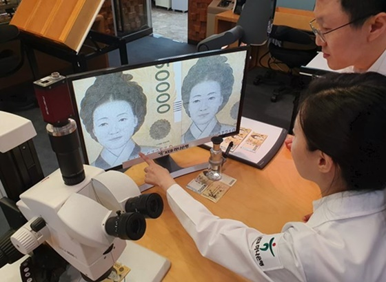 KEB하나은행 위변조대응센터 직원들이 진폐와 위폐를 정밀 감정하고 있다. (사진 = KEB하나은행)