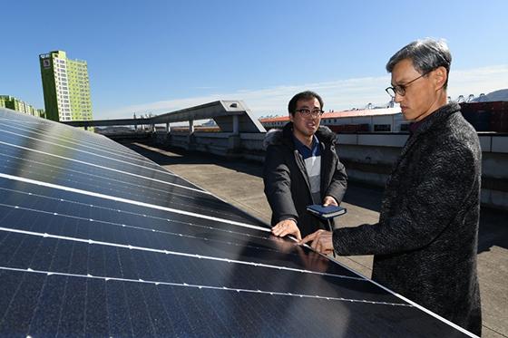 건물 옥상에 설치된 태양광 패널을 살펴보고 있는 SK에너지 조경목 사장 (사진 = SK에너지)