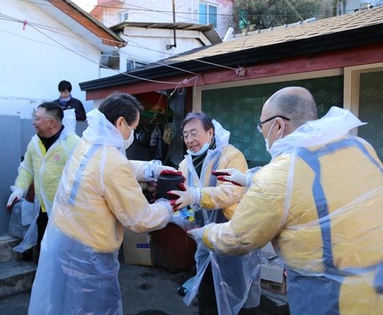 아성다이소 박정부 회장 및 임직원들이 2일 강원도 삼척시 도계읍을 찾아 소외계층 가정에 연탄을 나르고 있다. (사진 = 아성다이소)