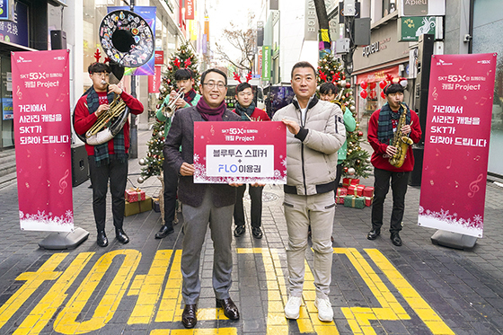 SK텔레콤 유영상 MNO사업부장(사진 왼쪽)이 명동복지회 임원 이강수 씨에게 캐럴 스트리밍용 블루투스 스피커를 전달하고 있다. (사진 = SK텔레콤)