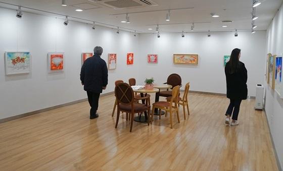 유디치과(강남뱅뱅 유디치과의원)를 찾은 환자들이 유디갤러리에서 작품을 관람하고 있다. (사진 = 유디치과)