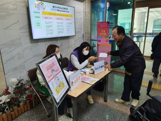용인시 처인노인복지관 직원들이 어르신들에게 마스크를 나눠주고 있다. (사진 = 용인시)