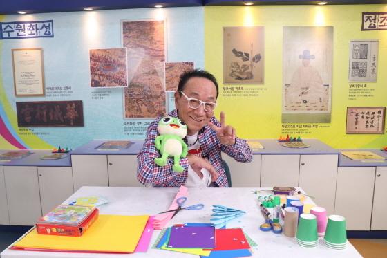 김영만씨가 수원시 공식 캐릭터 수원이 인형과 함께 기념촬영을 하고 있다. (사진 = 수원시)