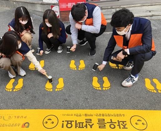 소상공인시장진흥공단 직원들이 어린이보호구역 횡단보도 앞에서 노란 발자국을 설치하고 있다. (사진 = 소진공)