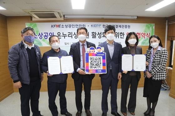 소상공인연합회와 한국간편결제진흥원 참석자들이 제로페이 태그를 들고 기념촬영을 하고 있다. (사진 = 소공연)