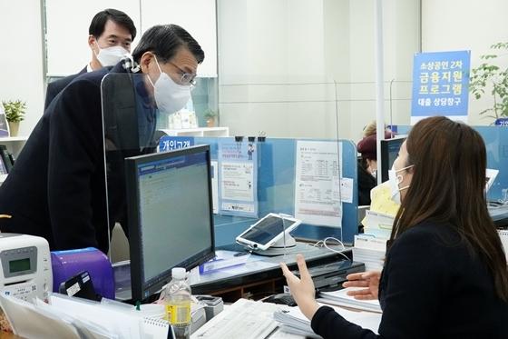 은성수 금융위원장이 기업은행 공덕동 지점을 방문해 설명을 듣고 있다. (사진 = 금융위원회 제공)