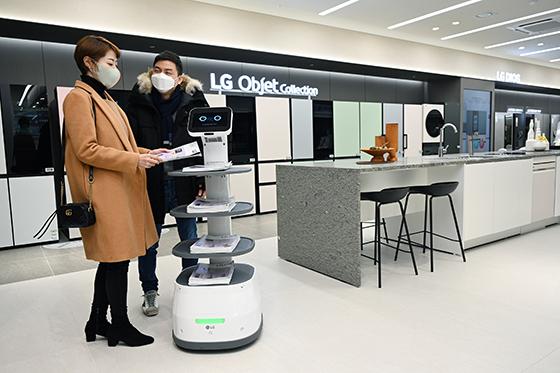 LG베스트샵 서초본점을 방문한 고객들이 LG 클로이 서브봇이 가져다주는 안내책자를 살펴보고 있다. (사진 = LG전자)