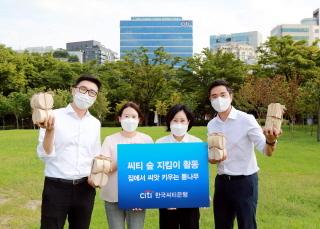 14일 유명순 한국씨티은행장(오른쪽 두번째)이 활동에 참여하는 직원들과 함께 집씨통(집에서 씨앗 키우는 통나무) 나무화분을 들고 기념촬영을 하고 있다. (사진 = 씨티은행)